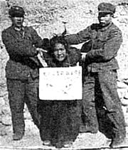A Tibetan women being subjected to a struggle session (a form of public humiliation in which the victim must confess to supposed crimes and wear a sign stating their misdemeanor) circa 1958